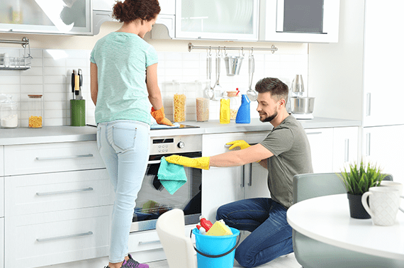 bearded man wiping oven handle with rag and woman wiping the gas stove
